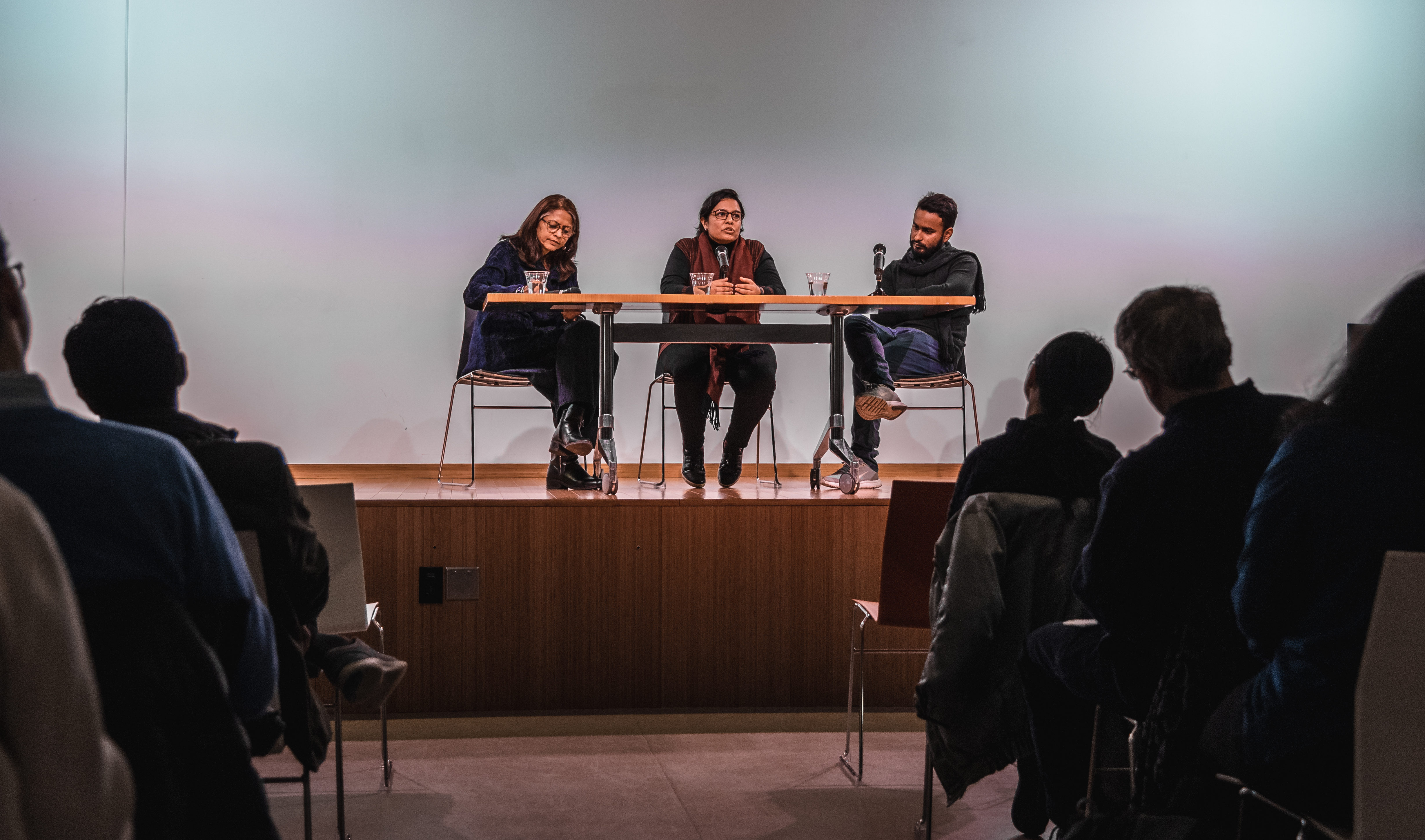Meena Sonea Hewett, Mittal Institute Executive Director (left), speaks with Visiting Artist Fellows Krupa Makhija (center) and Mahboob Jokhio (right) on stage about their work at a crowded gallery exhibition.